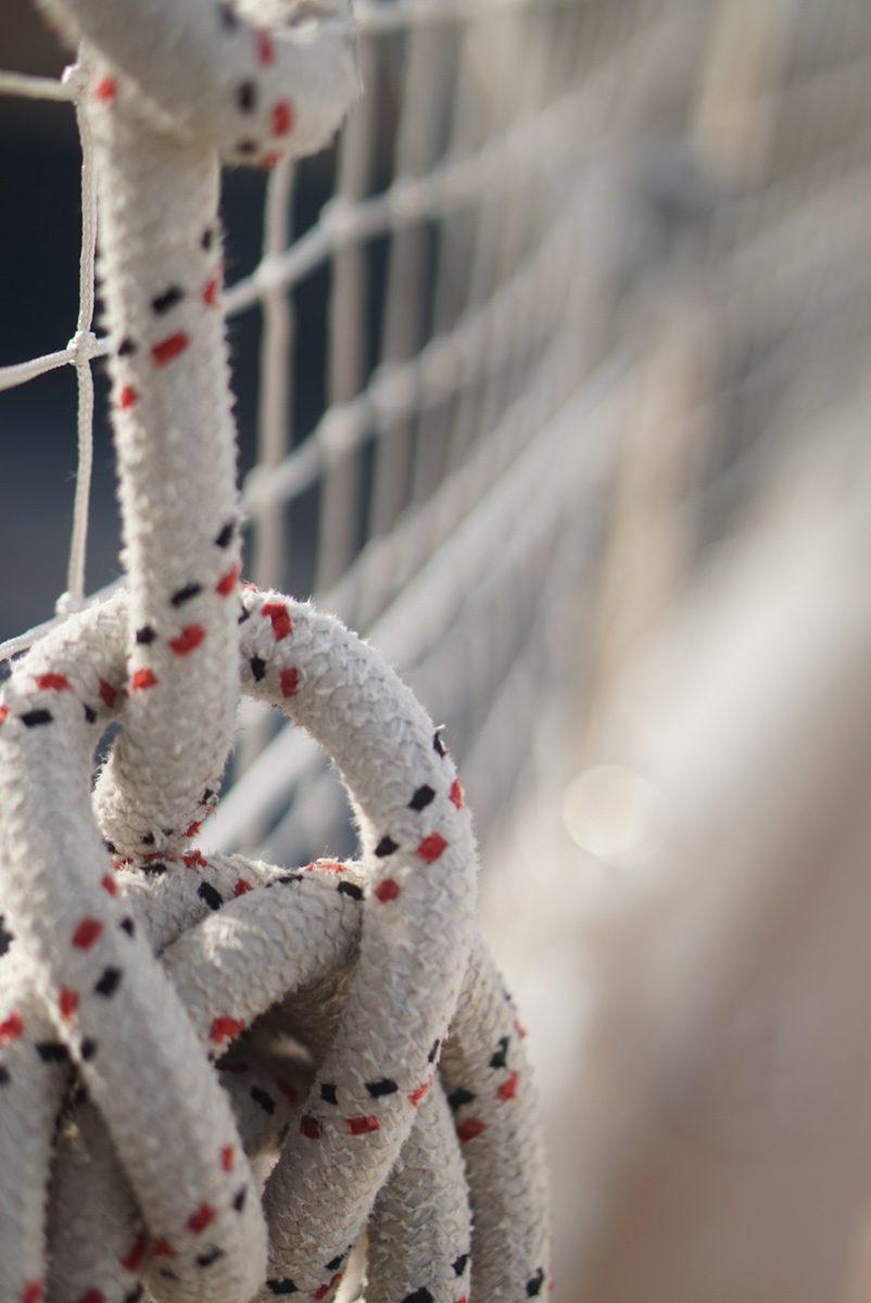 Nahaufnahme eines seemännischen Knotens des Tauwerks an Deck eines Schiffes im Sonnenlicht